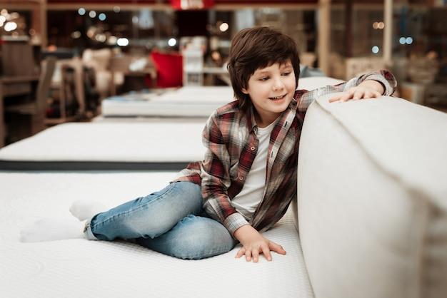 マットレス店でベッドに横になっている笑顔の小さな男の子