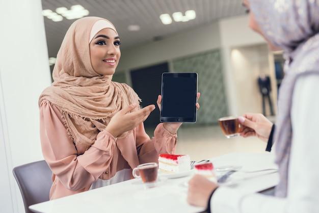 モダンなモールのカフェに座っている若いアラビア女性