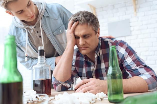Пьяный отец сидит за столом со стеклом