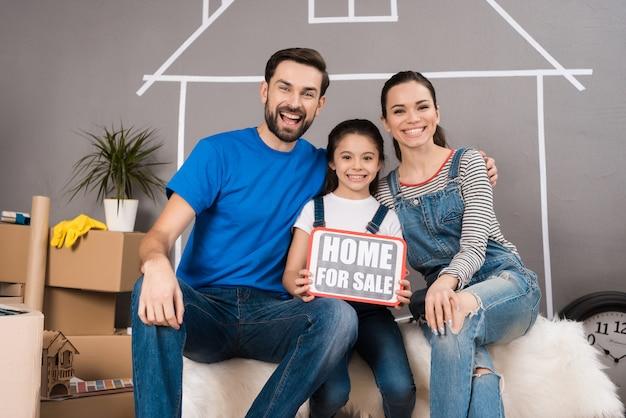 家族は家を売る。小さな女の子は販売と看板を持っています。
