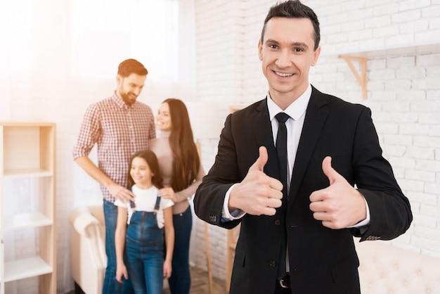 若い家族はアパートを見ます。前景の不動産業者。