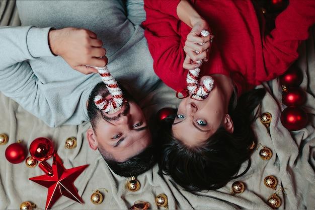 幸せな男と女はクリスマスツリーを飾る、男と女はキャンディーの杖を手に保持します。