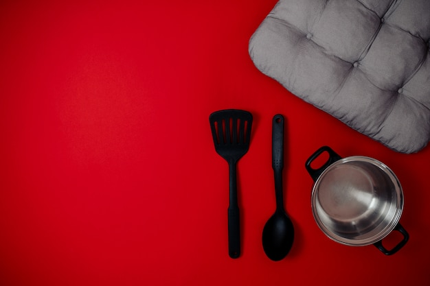 Черная пятница, продажа плоской планировки, баннер для товаров для дома, серебряная кастрюля, шпатель, большая ложка на красной поверхности,