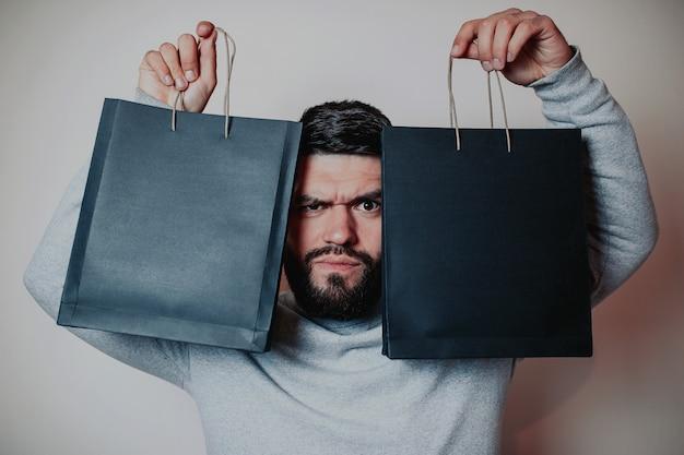ブラックフライデーセールフラットレイ、ブラックフライデーバッグ、黒い紙袋のひげを生やした男
