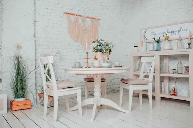 白いダイニングルームのインテリア。花、キャンドル、カップの白い丸いテーブル。
