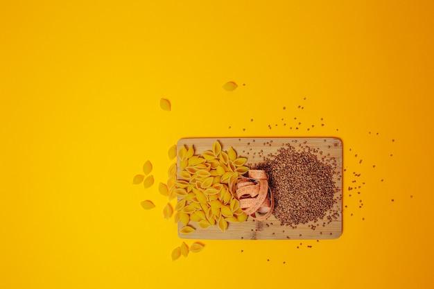 Диета и потеря веса тема. гречневая, макаронные изделия и рулетка на деревянной разделочной доске. медленные углеводы.