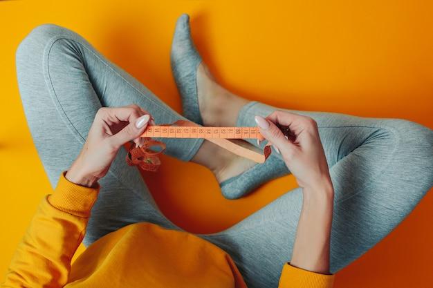 ダイエットと減量のテーマ。女性は測定テープを保持しています。ダイエット中の女性。