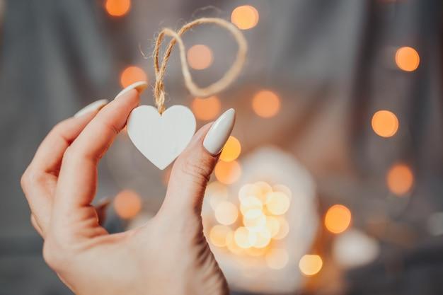 聖バレンタインの日カード。女性は、明るい背景に多くの白い木製の心を保持しています。ガーランドライトボケ味を持つ心。