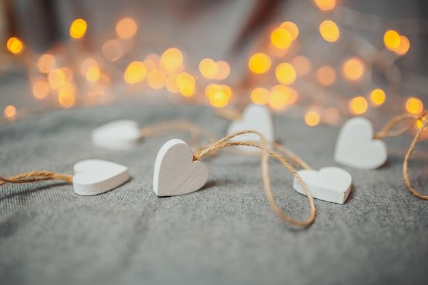 聖バレンタインの日カード。灰色の背景に白い木製の心。ガーランドライトと心。明るいボケ。