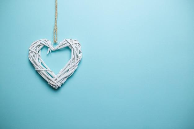 Большое белое деревянное плетеное сердце на веревочке с космосом экземпляра. день святого валентина карты на синем фоне.