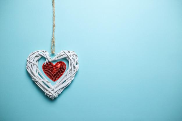 Большое белое деревянное плетеное сердце с малым красным сердцем блесток на веревке с космосом экземпляра. день святого валентина карты на синем фоне.