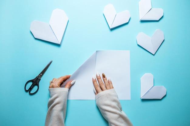 紙とハサミを中心に青色の背景に多くの白い折り紙の心。青の背景に折り紙の心を作る女性と聖バレンタインの日カード。