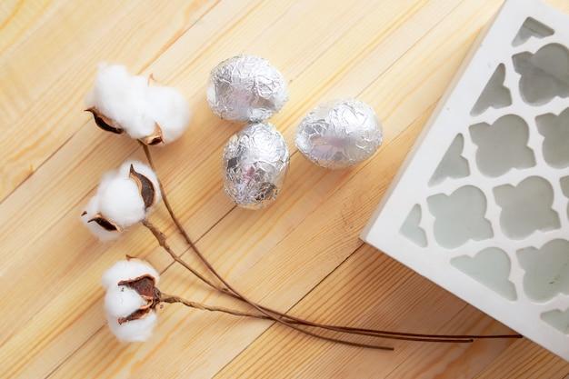 白い木製のテーブルのイースターエッグ。周りの花とキャンディー。