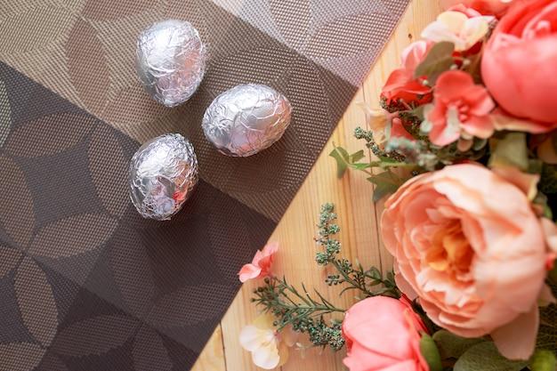 Пасхальные яйца на белом деревянном столе. цветы и конфеты вокруг.