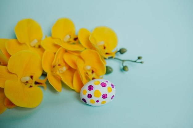 点線のイースターエッグと黄色の蘭。ハッピーイースターカード。