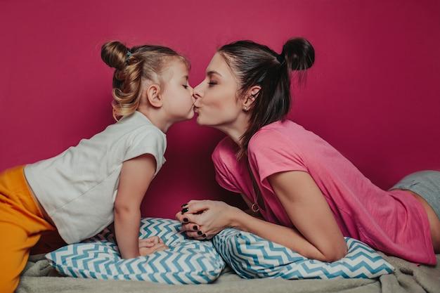 Мать целует дочь.