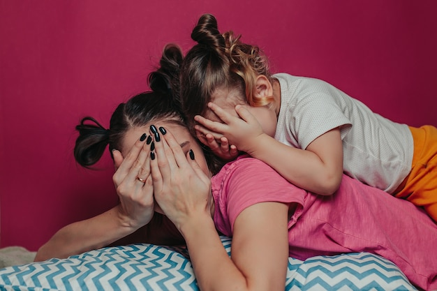 Мать и дочь прячутся с руками.