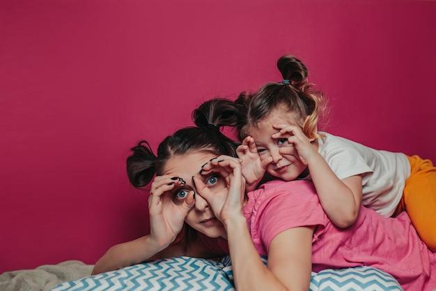 Мать и дочь делают лица.