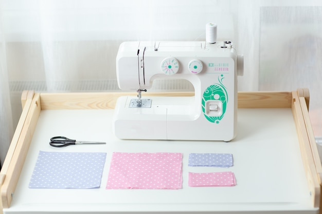 フェイスマスク、防護マスク縫製プロセス、点線の布、糸、ミシンを白いテーブルに縫う方法。