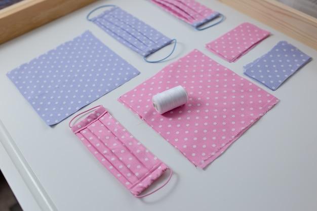 手作りのウイルスに対するフェイスマスク、防護マスク、点線の布の破片、白いテーブルのスレッドを縫います。ピンクとブルーの布、はさみと糸で平らに寝かせます。