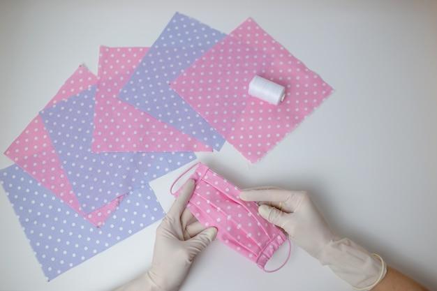 白いテーブルにフェイスマスク縫製の点線の布。防護マスクを縫う方法、白い手袋で女性の手は手作りの布マスクを保持します。
