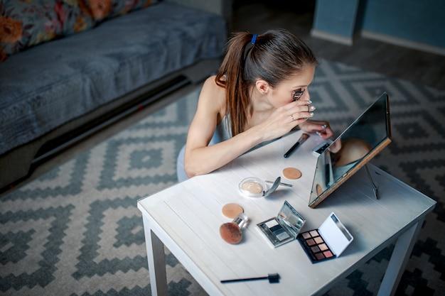 女性は鏡の前にまつげをカールします。女性は鏡の前に座っています。女性作るメイク