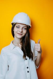 Женщина инженер в белом шлеме. плакат безопасности. женщина в белой рубашке и шлеме показывает большой палец вверх.