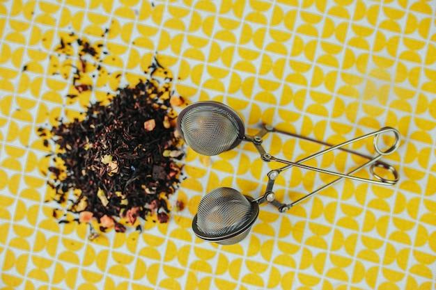 ティータイム、黄色いテーブルにメッシュティーステイナー、周りにリーフティー。