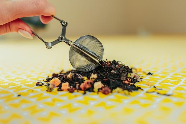 葉茶の周りの黄色のテーブルにメッシュ茶染色器。誰かがお茶のしみにお茶を入れます。