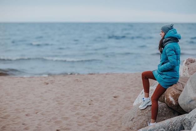 嵐の海岸の女性。海岸線の岩の上の女性。
