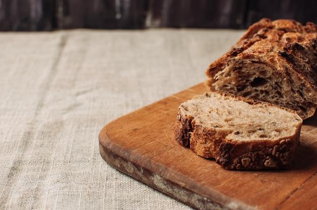 Темный гречневый хлеб без дрожжей в разрезе лежит на разделочной деревянной доске на деревянном столе