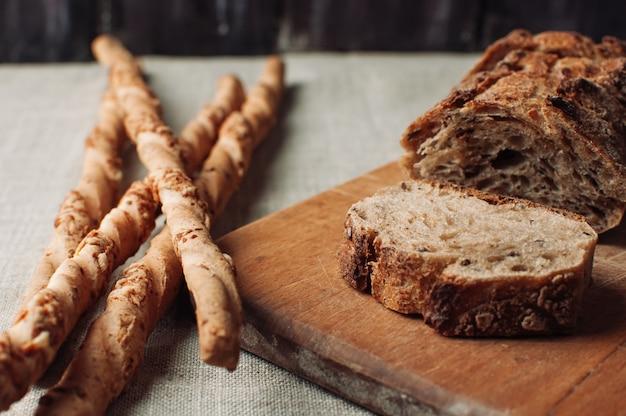 カットで暗い無酵母そばパンは、木製のテーブルにまな板の上にあります。