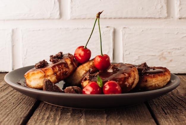 Сырники творожные блинчики с вишней и шоколадом на черном фоне с бетонным столом и белой кирпичной стеной.