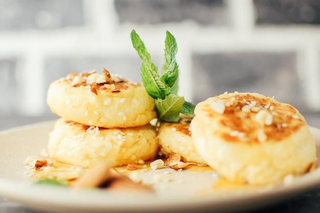 Чизкейки с миндальной свежей мятой и кленовым сиропом на сером фоне с бетонным столом.