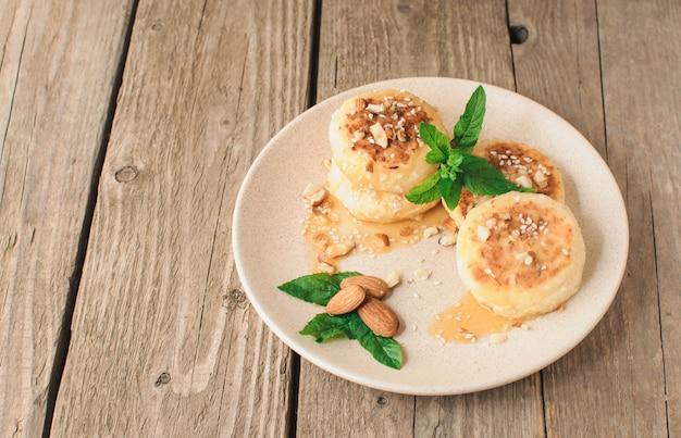 Творожные оладьи с миндалем, мятой и кленовым сиропом в бежевой тарелке.