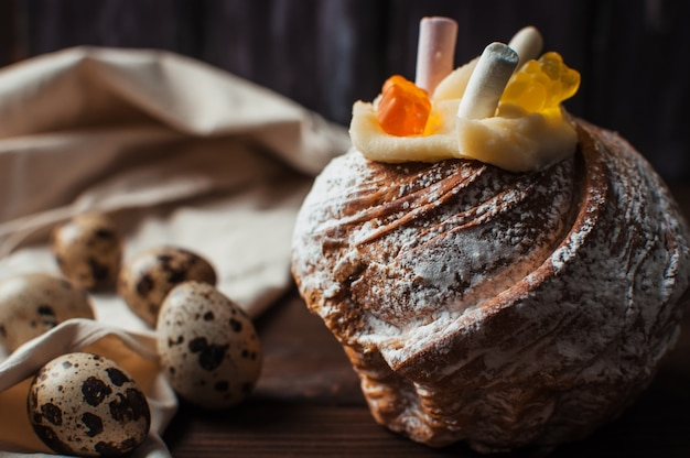 ウズラの卵の横にある木製の背景にマシュマロとゼリーのカップケーキ。