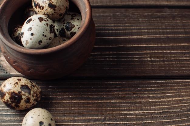 ウズラの卵は粘土のボウルにあり、いくつかの卵がテーブルの近くに横たわっています。