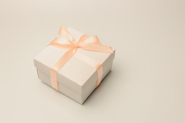 Подарочная коробка с бежевой лентой на белом фоне, изолировать.