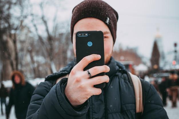冬の通りの日中にスマートフォンを使用して若い男のクローズアップ画像。