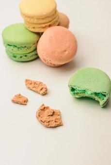 Зеленый миндальное печенье на переднем плане лежит прикус. рядом находятся крошки из французского теста.