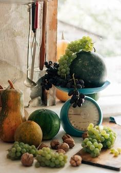 カボチャ、クルミ、メロン、スイカ、ブドウのスケールと木製の白いテーブルの上の秋の静物。