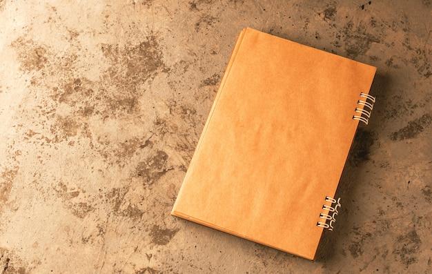 Тетрадь лежит на столе в открытом виде. макет для написания текста. спиральная тетрадь в крафт-бумаге.