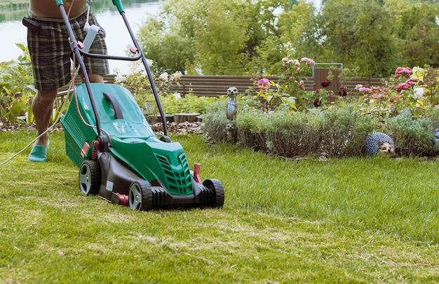 男は、夏に花の庭の近くの自分の庭で緑の芝生のある芝刈り機を刈っています。