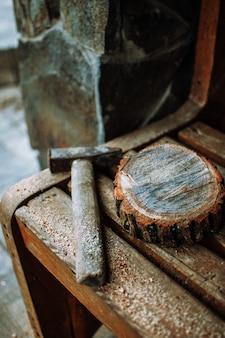 Старый старинный молоток и круглый брус сосны с опилками на скамейке.