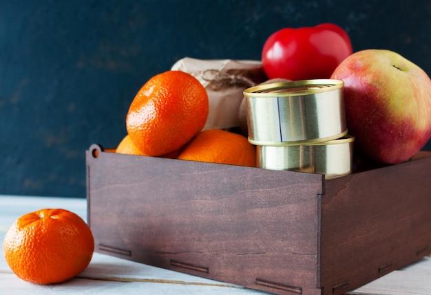 Курьер доставил коробку с едой во время пандемии коронавируса. в коробке находятся фрукты, овощи, консервы. благотворительная концепция. копировать пространство