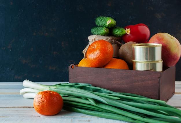 Курьер доставил коробку с едой во время пандемии коронавируса. в коробке находятся фрукты, овощи, консервы, лук. благотворительная концепция. копировать пространство