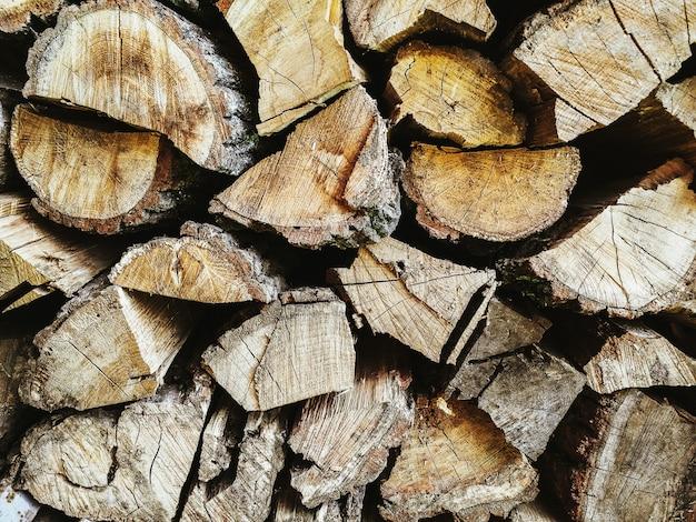Светлый деревянный фон. колотые дрова для камина лежат в каменной камере для материалов для костра. место для текста. шаблон для дизайна и надписей.