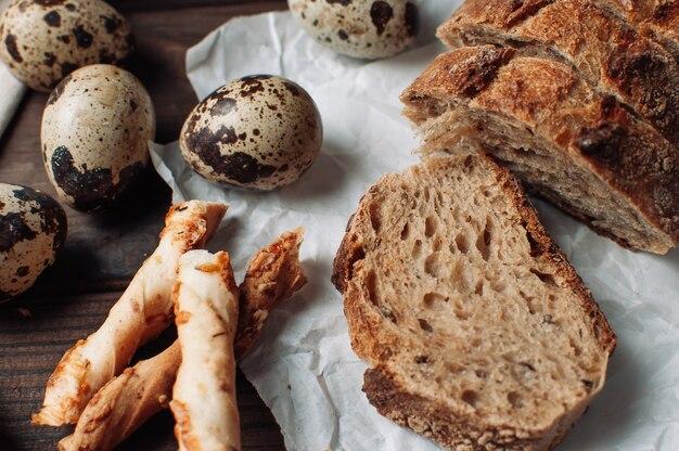 素朴なスタイルの木製のテーブルのリネンのテーブルクロスにウズラの卵とイタリアのグリッシーニの横にある羊皮紙にあるカットの嘘に暗いイーストフリーソバパンを設定します。朝食料理のコンセプトです。