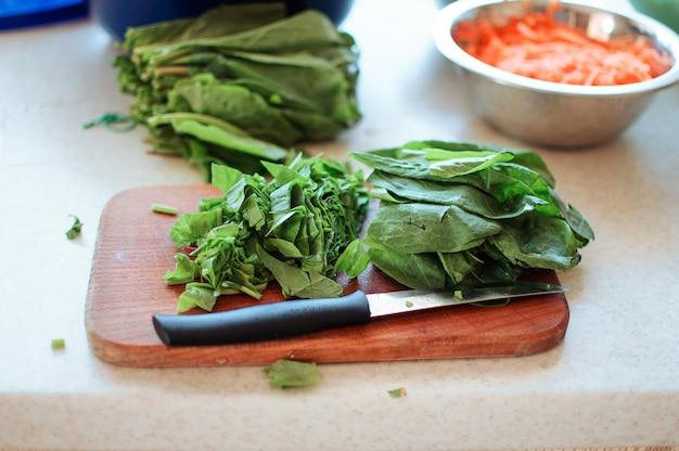 Зеленый щавель нарезанный на разделочную доску