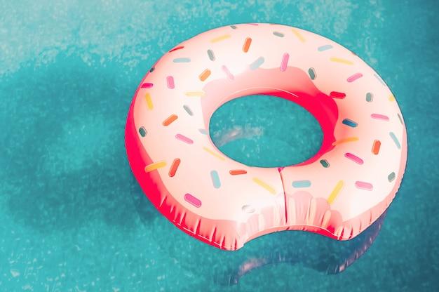 Надувной розовый пончик с белой глазурью плавает в бассейне